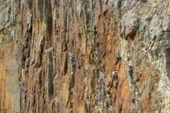 Grimpeur de roche audacieux sur le visage de falaise Image libre de droits