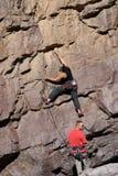 Grimpeur de roche avec le belayer Image stock