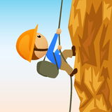 Grimpeur de roche de dessin animé sur le cliffside vertical Photographie stock libre de droits