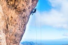 Grimpeur de roche escaladant la falaise surplombante  image libre de droits