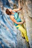 Grimpeur de roche escaladant une falaise image stock