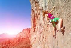 Grimpeur de roche féminin de la jeunesse accrochant sur le mur vertical Photographie stock