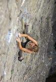 Grimpeur de roche féminin luttant sa voie vers le haut d'une falaise Photo stock
