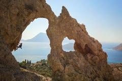 Grimpeur de roche féminin supérieur sur une falaise image stock