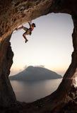 Grimpeur de roche féminin au coucher du soleil Images stock