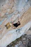 Grimpeur de roche montant une falaise provocante Climbi extrême de sport image stock
