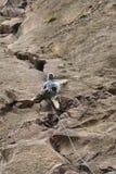 Grimpeur de roche s'attachant à une falaise Photographie stock