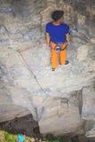 Grimpeur de roche se reposant sur une roche Photos libres de droits