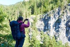 Grimpeur féminin faisant la photo de la roche verte spectaculaire avec de hauts arbres sur le dessus photographie stock