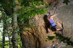 Grimpeur féminin s'élevant avec la corde sur un mur rocheux Photos libres de droits