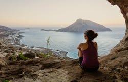 Grimpeur féminin s'asseyant dans la caverne et le coucher du soleil de observation images libres de droits