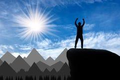 Grimpeur heureux de silhouette sur un dessus de montagne Images stock