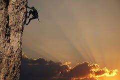 Grimpeur sur le coucher du soleil sur la roche Photo stock