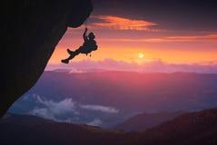 Grimpeur sur le fond de coucher du soleil Images libres de droits