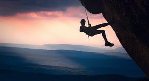 Grimpeur sur une falaise contre les montagnes brumeuses Photo libre de droits