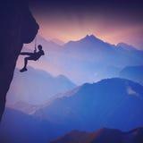 Grimpeur sur une falaise contre les montagnes brumeuses Couleurs de vintage Photos stock