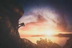 Grimpeur sur une roche contre le coucher du soleil r Images stock