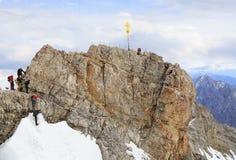 Grimpeurs à la croix sur le sommet de la montagne de Zugspitze, Allemagne photographie stock
