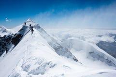 Grimpeurs équilibrant dans la tempête de neige Photographie stock libre de droits