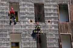 grimpeurs audacieux et audacieux des sapeurs-pompiers montant une maison photo libre de droits