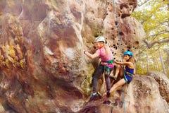 Grimpeurs dans les casques avec l'avance montant la roche Image libre de droits