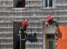 grimpeurs des sapeurs-pompiers escaladant un mur d'une maison pendant le f image libre de droits