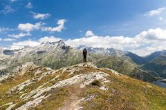 Hiker standing on the Alps mountain. Grimsel, Switzerland - August 12, 2018: Hiker standing on the Alps mountain peak looking into the Grimsel valley stock photo