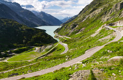 Grimselpass. Scenic view down the Grimselpass in Switserland, with the road leading down to the lake reservoir Stock Photo