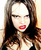 Angry woman with grin on face. Disheveled glossy hair  and bright makeup furiously looks at camera Royalty Free Stock Images