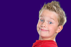 Grin. Happy boy in front of blue background stock photo