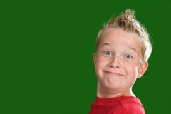 Grin. Happy boy in front of green background stock photo