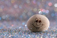 The grin stone emoji. Emotions on color glitter boke background royalty free stock photos