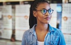 Grina den unga kvinnan i glasögon som över ser Royaltyfria Foton