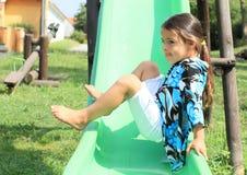 Grina flickan på en glidbana Royaltyfri Foto