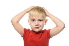 Grina vek den blonda pojken i en röd t-skjorta hans armar bak hans huvud Isolat på vitbakgrund royaltyfri foto