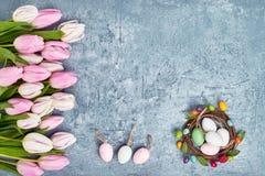 Grinalda da Páscoa, beira de tulipas cor-de-rosa e ovos da páscoa decorativos no fundo azul Vista superior, espaço da cópia Fotografia de Stock