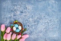 Grinalda da Páscoa, tulipas cor-de-rosa e ovos da páscoa decorativos no fundo azul Vista superior, espaço da cópia Imagem de Stock Royalty Free
