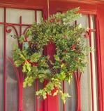 Grinalda do azevinho do Natal em uma porta vermelha Fotos de Stock Royalty Free
