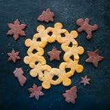 Grinalda do homem de pão-de-espécie e formas diferentes das cookies em um blac Foto de Stock Royalty Free