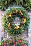 Grinalda do Natal com os cones das laranjas, do azevinho e do pinho fotos de stock royalty free