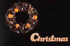 Grinalda do Natal e escrita de madeira do Natal no preto Imagens de Stock