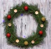 A grinalda do Natal do pinho ramifica com velas em um fundo de madeira branco, bolas do Natal, espaço da cópia imagens de stock royalty free