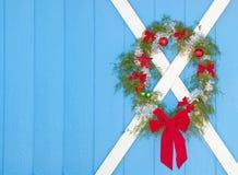 Grinalda do Natal que pendura em uma porta azul Fotos de Stock