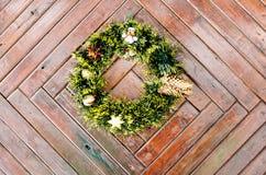Grinalda do Natal que pendura em uma porta de madeira no inverno Foto de Stock Royalty Free