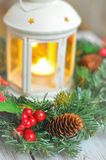 Grinalda do ` s do ano novo de um abeto em um fundo de madeira branco e em uma vela em um castiçal branco Fotos de Stock Royalty Free