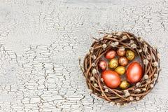 Grinalda do salgueiro da Páscoa e ovos da páscoa coloridos na tabela branca Vista superior Foto de Stock