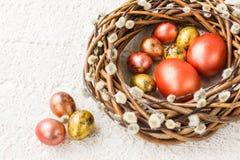 Grinalda do salgueiro da Páscoa e ovos da páscoa coloridos na toalha de mesa branca Vista superior Fotografia de Stock Royalty Free