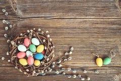 Grinalda do salgueiro da Páscoa e ovos da páscoa decorativos coloridos no fundo de madeira velho Copie o espaço Fotos de Stock