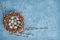 Grinalda do salgueiro da Páscoa e ovos da páscoa decorativos no fundo azul Vista superior, espaço da cópia Foto de Stock Royalty Free