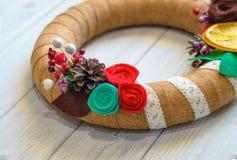 A grinalda e a fita do Natal curvam-se em um fundo da placa de madeira Fotos de Stock Royalty Free